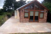 New patio area laid with Bradstone sunset buff sandstone slabs and paved areas using Woburn rumbled Autumn Blocks
